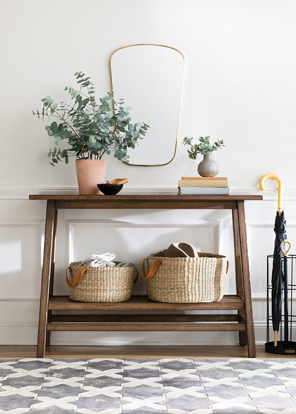 An entryway table is decorated with faux greenery in vases and a mirror