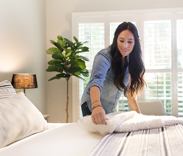 Joanna Gaines adds a cream throw blanket to the end of a bed