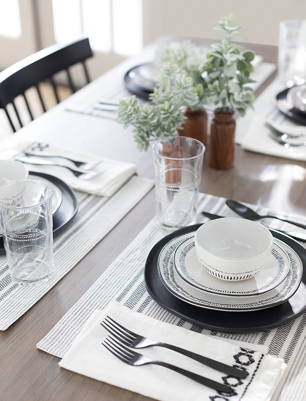 A table is set with Hearth & Hand dinnerware, utensils, greenery stems, glasses and more