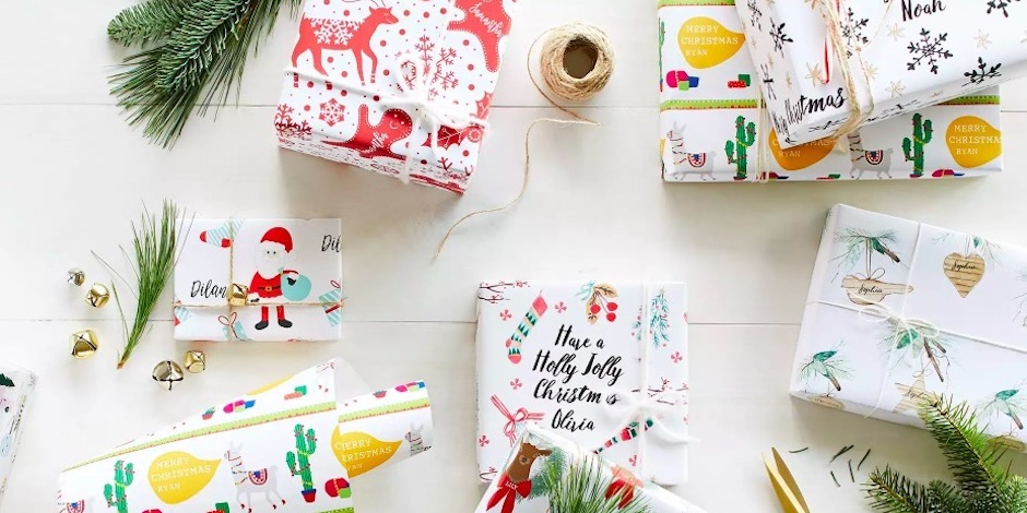 Six festively wrapped gifts tied with strings and jingle bells on a white wood table