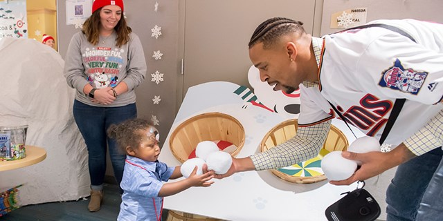 A Minnesota Twins player hands faux snowballs to a little girl as a volunteer looks on