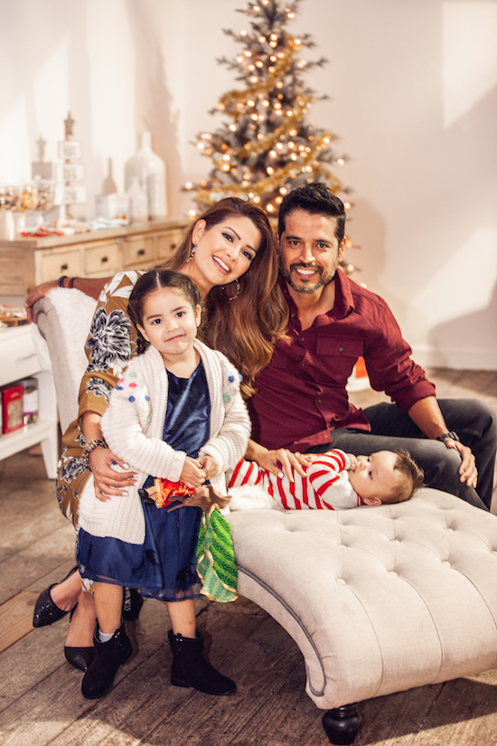 Ana Patricia and her husband and two kids cuddle together  on a chaise in front of a shiny, golden Christmas tree