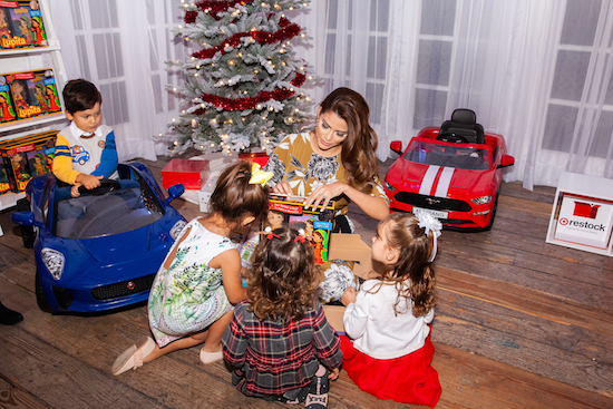 Ana Patricia sits under a decorated Christmas tree helping four children unwrap gifts
