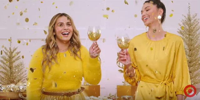 Two women in gold outfits laugh and raise gold-sparkling glasses in a toast while confetti falls