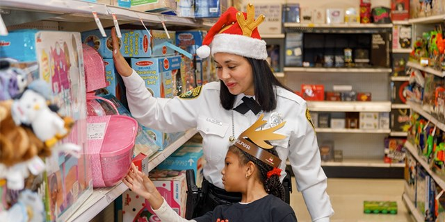 An officer in a Santa hat helps a young girl looking at gifts on a toy shelf reach a pink package