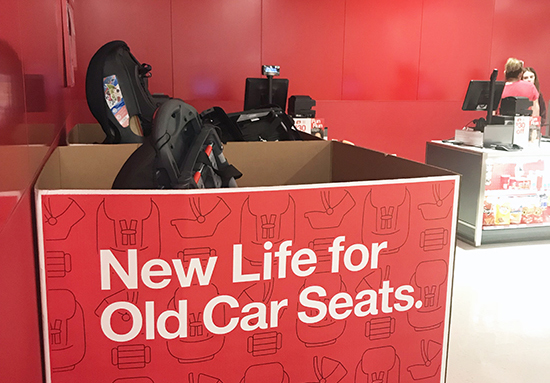 A large red cardboard box filled with used Car seats reads: New Life For Old Car Seats in white text