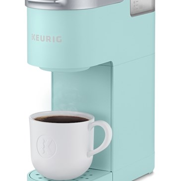 A mint green coffee maker with silver top and a white cup of coffee