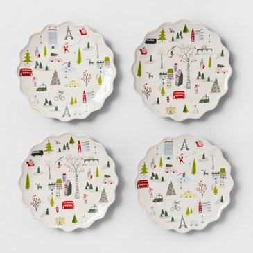 A set of four white plates with colorful print and scalloped edges