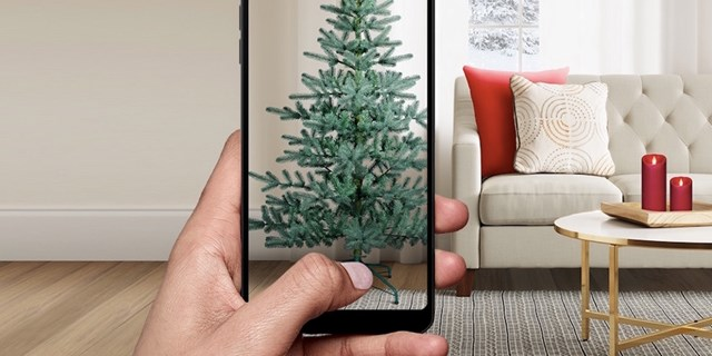 A hand holding a smartphone showing a tree against the background of a living room setting