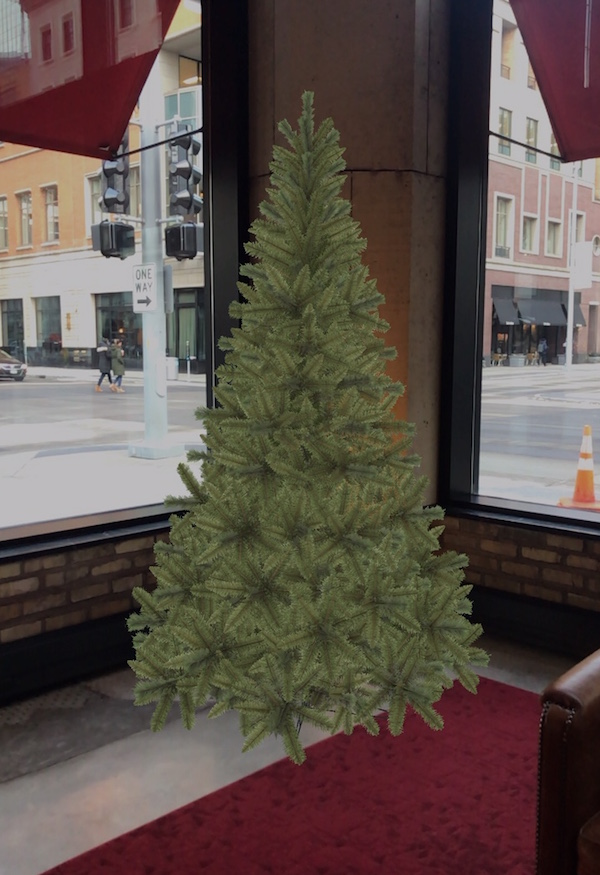 A augmented reality image of a Christmas tree in the corner window of a lobby