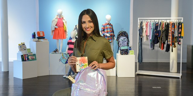 Karla packing a purple iridescent backpack