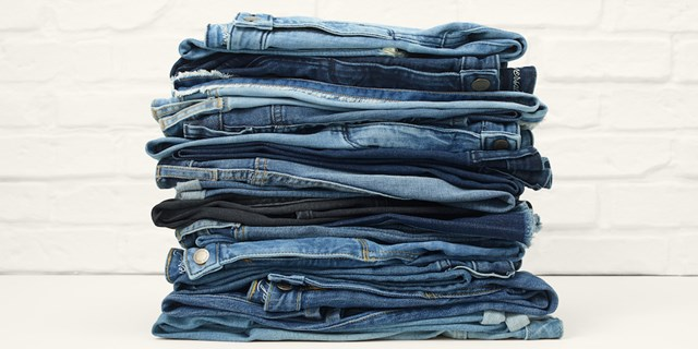 Stack of folded jeans on a white background