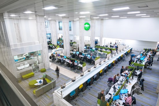 aerial view of open office with desks, chairs, technology and people