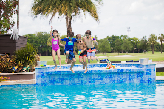 Kids jumping into a swimming pool wearing Cat & Jack swim