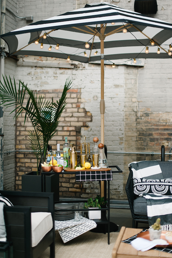 A bar cart and a black and white umbrella