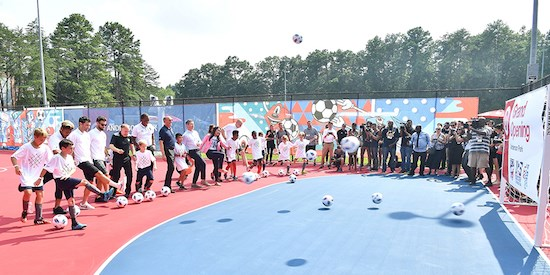 red and blue soccer pitch with colorful murals and kids playing soccer