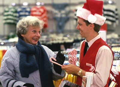 archive photo of a team member in santa hat handing a candy cane to a guest