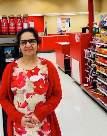 team member Gulzar in a tan dress with flowers and red cardigan