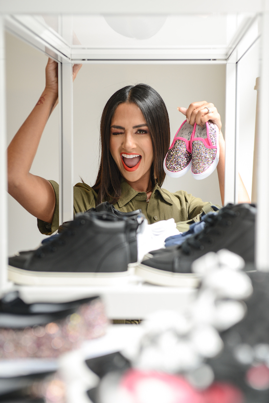 Karla holding up a pair of pink glittered slip-on sneakers