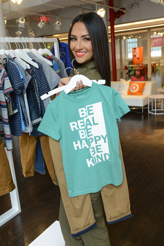 Karla holding up a graphic tee and khaki pants