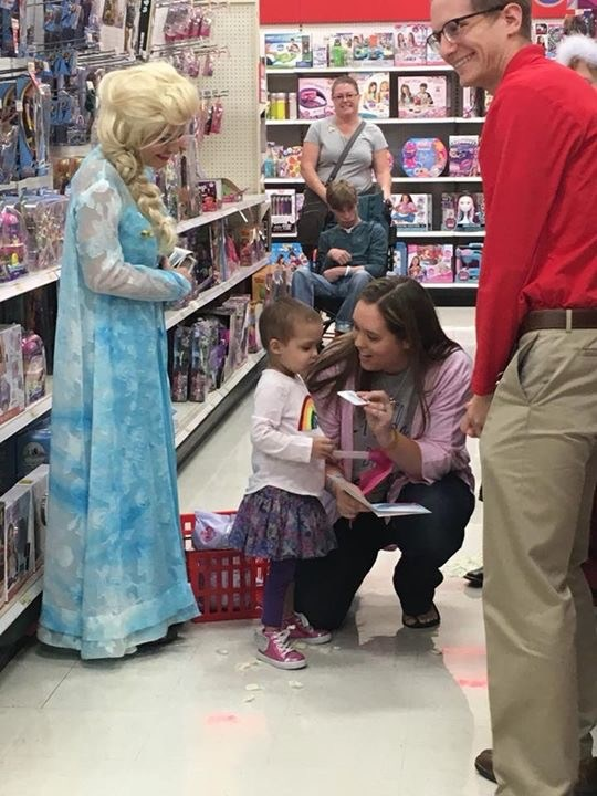 Frozen character and family share gifts with little girl at an in-store party