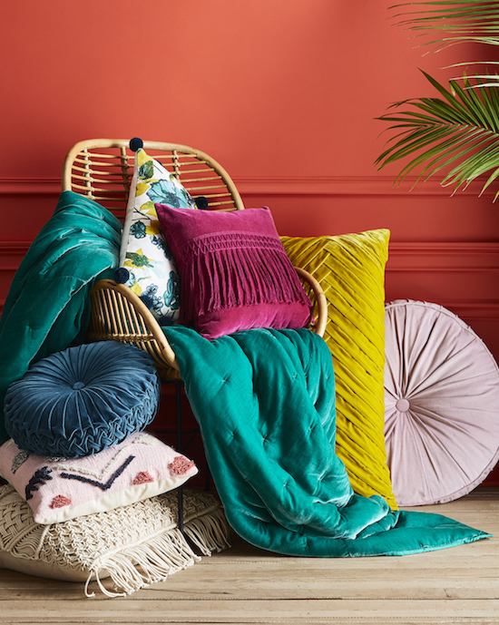 Throw pillows and blankets on a wooden chair