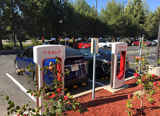 Two cars recharging at Tesla stations