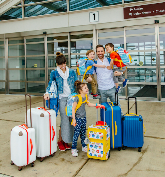 Naomi Davis and family outside an airport with the Love Taza luggage collection