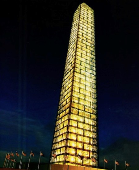 Washington Monument at night while covered in scaffolding designed by Michael Graves