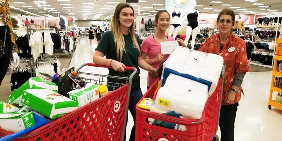 Team member Mary stands with two partners with shopping carts filled with donated supplies