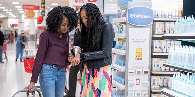 Camille and Emerald stand in Target's beauty aisles testing a product on the back of their hands
