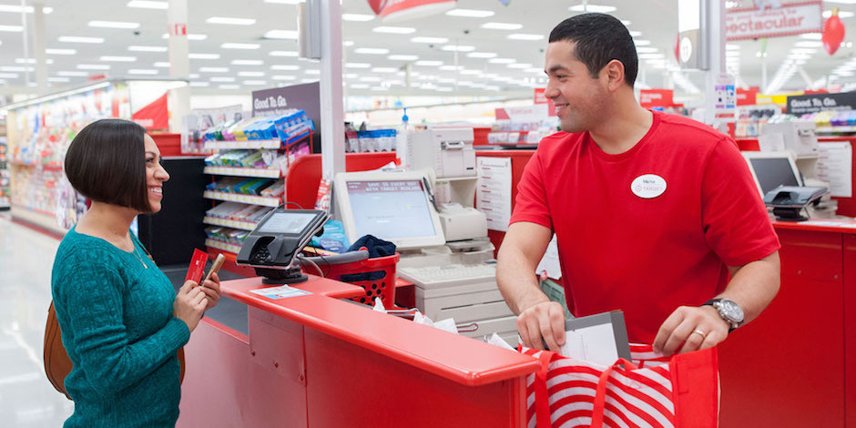 A team member bags a guest's purchase as she pays at the checkout counter