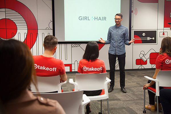 Josef stands at the head of a classroom presenting to other Target Takeoff members in front of a big screen that reads Girl + Hair