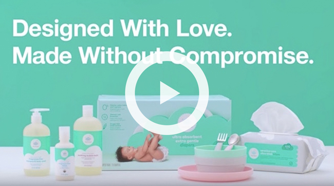 "A variety of baby essentials on a green background, with the words ""Designed With Love. Made Without Compromise."""