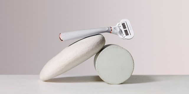 A white and rose gold Flamingo razor balances atop two white stones against a white background