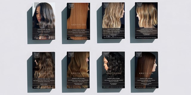 Eight boxes of Kristin Ess hair gloss against a grey background