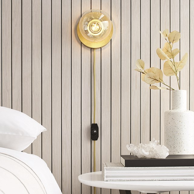 A golden wall sconce lights a bedroom scene