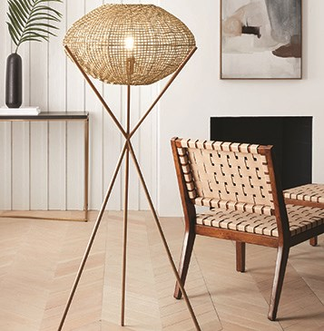 A woven floor lamp lights a living room