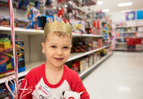A young boy in a red and white tee smiles, wearing a gold crown and hugging a white plush Bullseye dog. He's standing in a Target toy aisle.