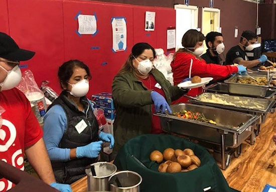 Six Target volunteers in masks serve food from pans at a shelter