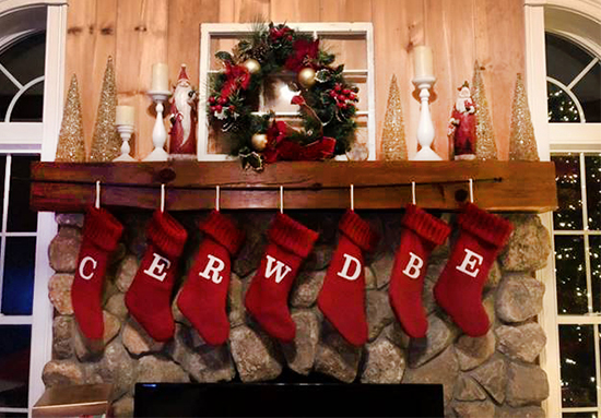 A festively decorated mantle holds seven red stockings with a white embroidered letter on each one