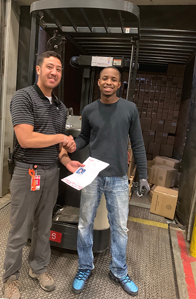 Aaron and manager Danny stand on the back of a trailer truck filled with boxes. They are shaking hands and holding a piece of paper that details the donation.