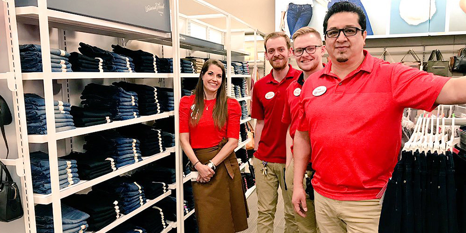 Four team members in red shirts standing in the denim section at Target