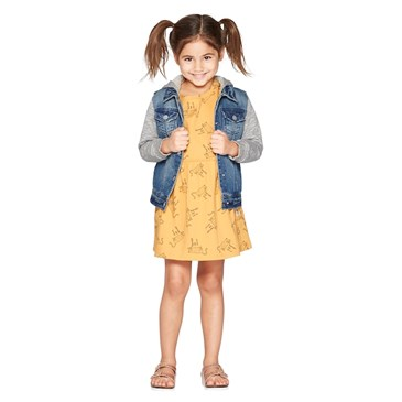 A model wears a yellow dress and denim jacket with gray sleeves