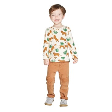 A model wears a cream shirt with orange and green animal print and orange pants