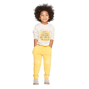 A model wears a cream and yellow printed top and yellow pants