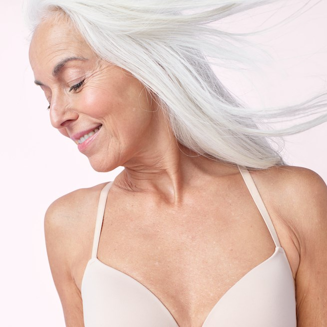 A woman models a cream bra