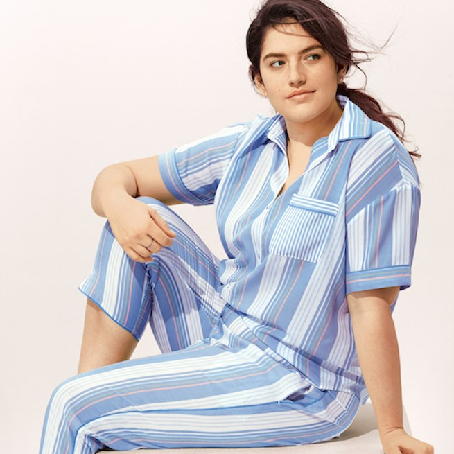 A woman models a blue stripped pajama set
