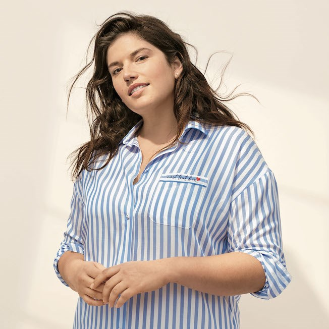 A woman models a white and blue stripped sleep shirt