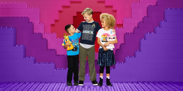 Three kids wearing LEGO gear stand in front of giant pink, red and purple LEGO bricks